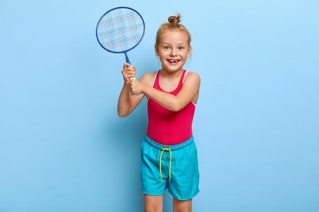 pige i badmintontøj og med ketcher